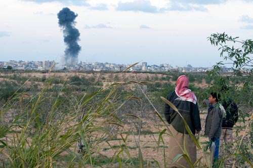 A father and son look on from a hilltop on the Egyptian side of the Rafah border terminal as Israeli jets bomb Rafah City, Gaza, on Friday, January 9.