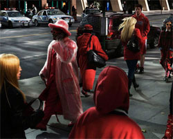 People on city street, all wearing red.