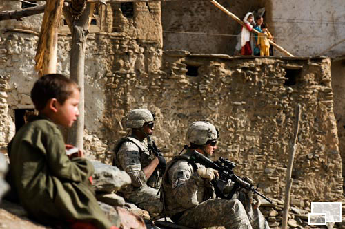 A pair of U.S. soldiers sit down on a steep hillside in a village. An Afghan boy sits nearby, and a woman and her children watch from afar.