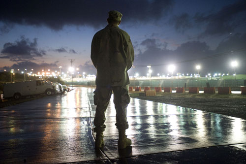 A soldier, back to the camera, stands amid the glare of lights reflecting off the wet concrete.
