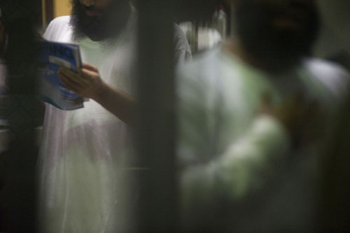 Through a barred enclosure, a detainee can be seen reading a surfing magazine.