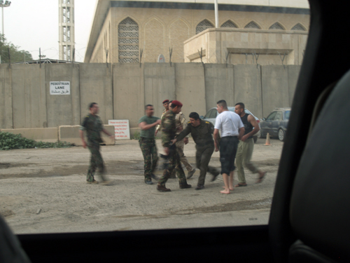 A group of Iraqi soldiers dressed in fatigues scuffle on the street.