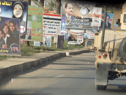 American armored vehicles convoy down abandoned streets and past rows of election posters.