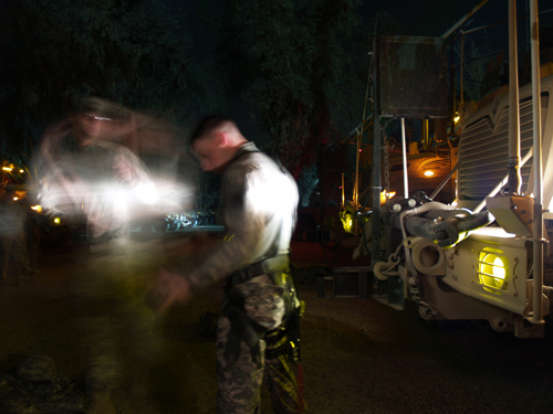American soldiers gear up by the headlights of their armored vehicles.