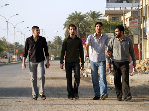 Four smiling men casually walk down the otherwise abandoned streets of Baghdad.