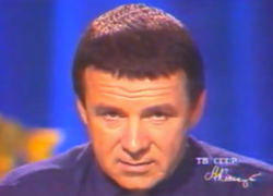 A man with a caesar haircut and a turtleneck stares into the camera.