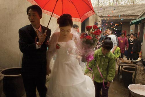 Young newlyweds share an umbrella