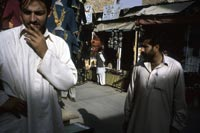 Quetta: Early morning shoppers examining clothing at a city bazaar.