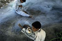Jiwani, Baluchistan: Mending fishing nets.