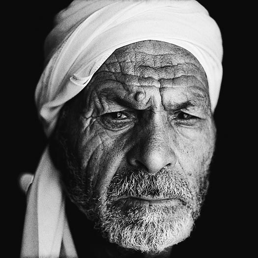 An old man wearing a turban gazes at the camera. His face is creased and leathery. He has a close-cropped salt-and-pepper beard.