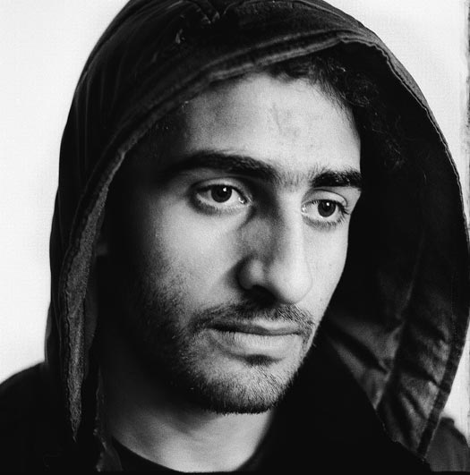 A young man with a light beard and a jacket with the hood raised.