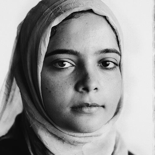 A girl, wrapped in a headscarf, with freckles and a round face.