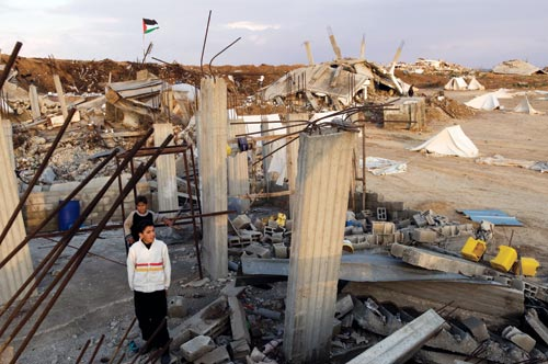 Two boys stand amidst rubble, with concrete pillars and rebar jutting up all around them.