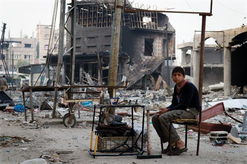 A sandal-wearing boy sits on a crude, battered chair, a small, equally-battered table before him. Behind him is the rubble of large, urban structures.