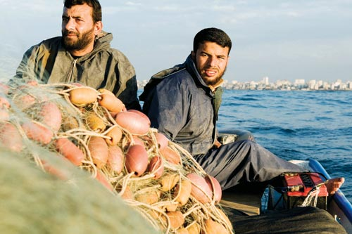 Two bearded men sit at at the stern of a boat. In front of them is a large bundle of netting and buoys.
