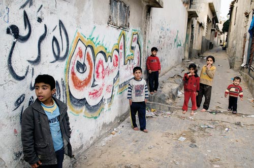 A group of young children congregate in an alley. Several of them are barefoot. The walls of the buildings are graffitied.