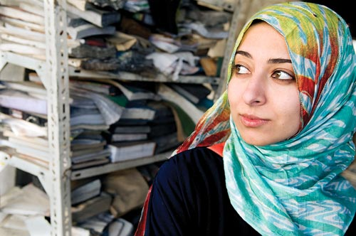 A young woman, wearing a headscarf, stands in front of a shelf weighed down with ragged books.