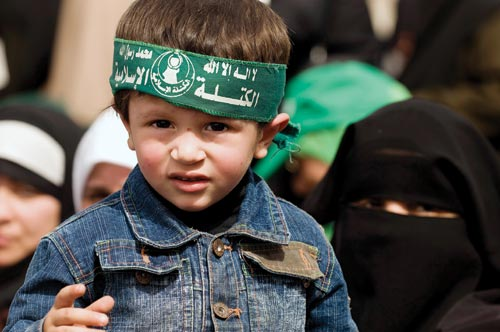 A young boy wears a green headband. Behind him are hijab-wearing women.