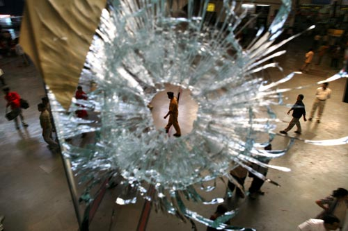 An officer patrols a train station, as seen through a bullet hole in glass above.