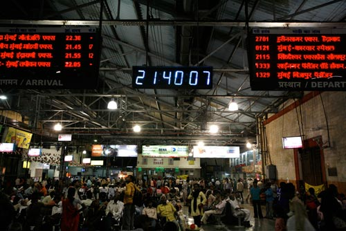 A train station is crowded with people. Arrival and departure boards loom over them, suspended from a corregated metal roof.