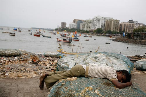 At the water's edge, a young man sleeps on a fishing net. Behind him is a filthy shore, and then a small inlet crowded with small boats. On the other side of the inlet is a cluster of squat high-rise buildings.