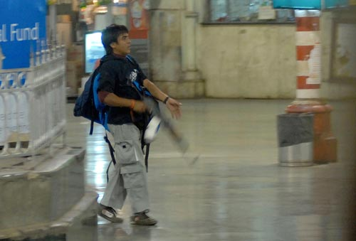 A young man walks through a train station. Nobody else can be seen. He's carrying a large backpack. In his right hand is a large rifle with a sizable clip of ammunition.