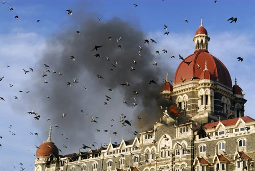An ornate, castle-like hotel is on fire, a cloud of black smoke rising to meet the blue sky. In the foreground, a flock of birds flies by.