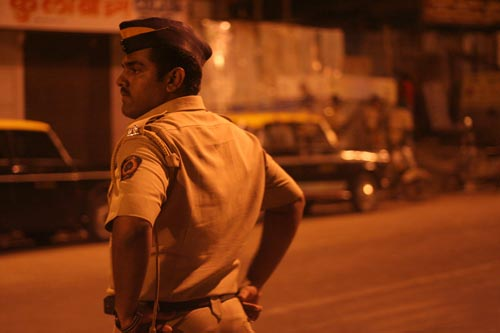 A police officer stands on the side of a street, hands on his hips.