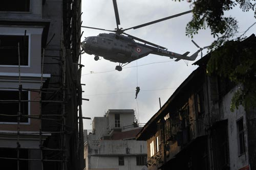 A man slides down a rope from a large helicopter onto the roof of a building.
