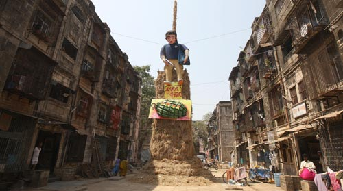 In a wide alley between rows of shabby four-story residential buildings, a three-story-tall hay bale pile supports an effigy of the Mumbai terrorist caught on camera, wearing his distinctive blue shirt, carry a backpack, and holding a silver gun. Below him is a large sculpture of a grenade.