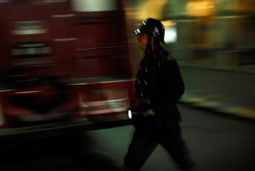 A man dressed in the manner of an English Bobby, carrying a flashlight, walks past a fire truck. His mouth is open, as if shouting.