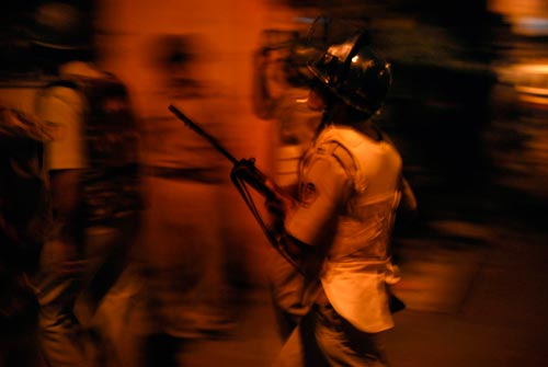 A trio of soldiers rush through the night, wearing bulletproof vests and helmets, carrying rifles.