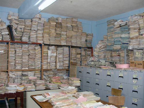 Stacks of documents fill a room