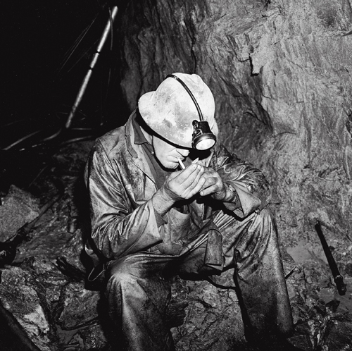 The late Lester Beattie smoking after drilling in a bypass drift at the 1,450-foot level of the Kerr Mine. Beattie suffered from 'white hand,' also known as Hand-Arm Vibration Syndrome.