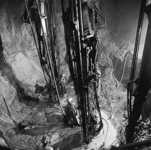 Shaft miners drilling a shaft with jumbo drills at the 2,500-foot level station of the Louvicourt Mine.