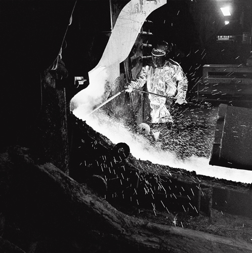 A furnace tapper using a thermal lance to test the purity of molten nickel. The furnace at the Falconbridge Smelter operates at over 1,000 degrees centigrade.