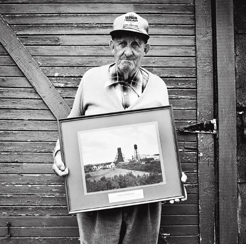 The late Jack Murnaghan, a retired union organizer, holding his retirement gift—a photo of the Macassa Mine where he had worked.