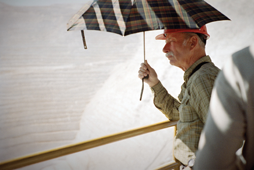 A German tourist surveys the Chuquicamata mine from beneath the shade of an umbrella; tours run regularly to the mine and to the nearby ghost town.