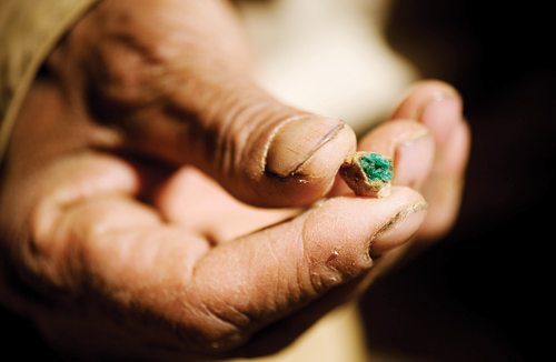Commander Jalaluddin holds a low-grade emerald outside a dormant mine.