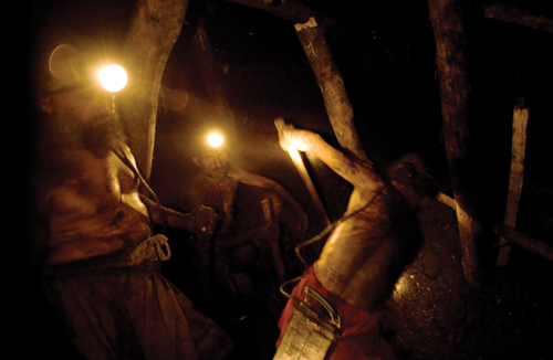 Workers shovel coal in the Karkara mine.