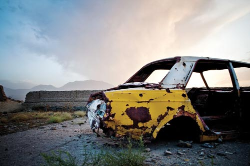 The rusted yellow-and-white body of a car, all other parts gone, rests on concrete. In the background is a mountain range, and the beginnings of a sunset.