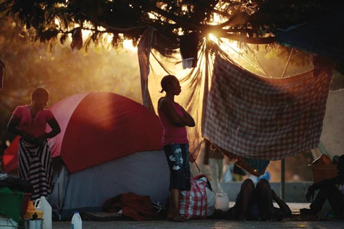Women stand in the orange, dying light in front of a tent. Jugs and bags are on the ground around them. In the background are more people and more tents.
