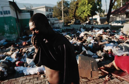 A brick plaza is covered with a tangle of bodies. A man walks by, holding his shirt up to cover his mouth and nose.