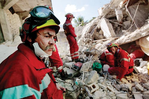 A half dozen red-suited, helmeted men surround a small opening in a pile of rubble.