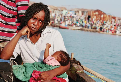 A serious-looking woman sits on a boat, head resting on her hand, holding a baby on her lap. The shore is only a few hundred yards away.