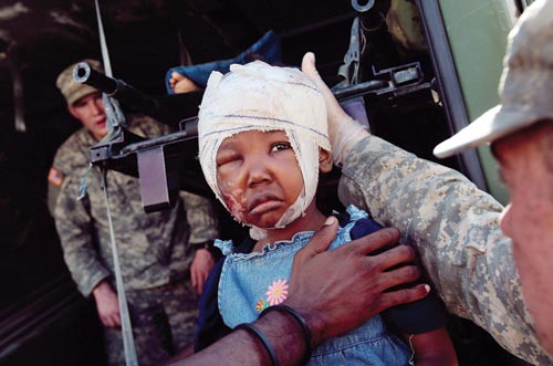 A sad little girl has her head bandaged, a scraped-up cheek, and one eye swollen shut.
