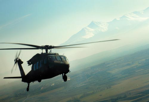 A large, olive-green helicopter whirs through the air. It's flying over a large, green plain. In the distance, craggy, snow-capped mountains rise into the sky.