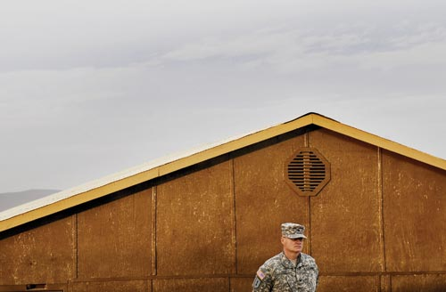 A uniformed American soldier stands at attention in front of a low building.