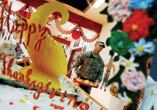 A man in a camouflaged uniform carries a food-laden tray down a hallway laden with Thanksgiving decorations.