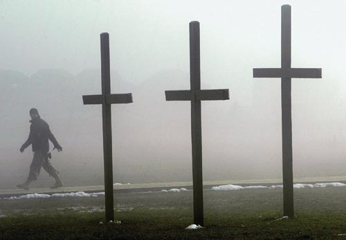 Three simple crosses, perhaps ten feet tall, are planted in the grass. Remnants of snow are near their base. In the background, a soldier walks by, obscured by fog.